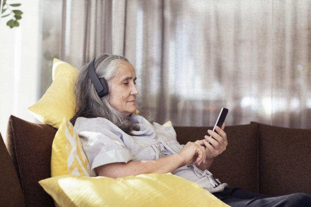 Kvinna lyssnar på musik i hörlurar